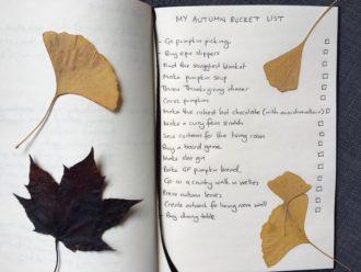 Handwritten autumn bucket list with colourful autumn leaves